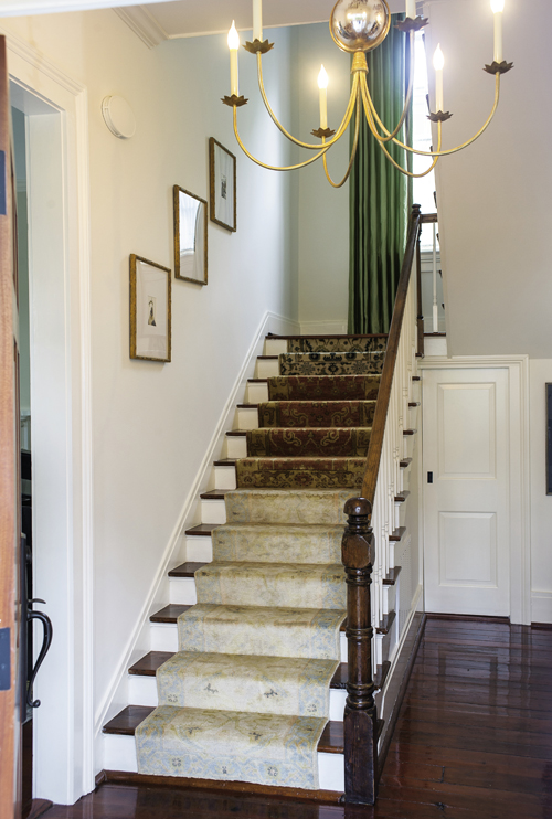 In the foyer, a runner composed of several antique and reproduction rugs sewn together strikes an eclectic welcoming note.