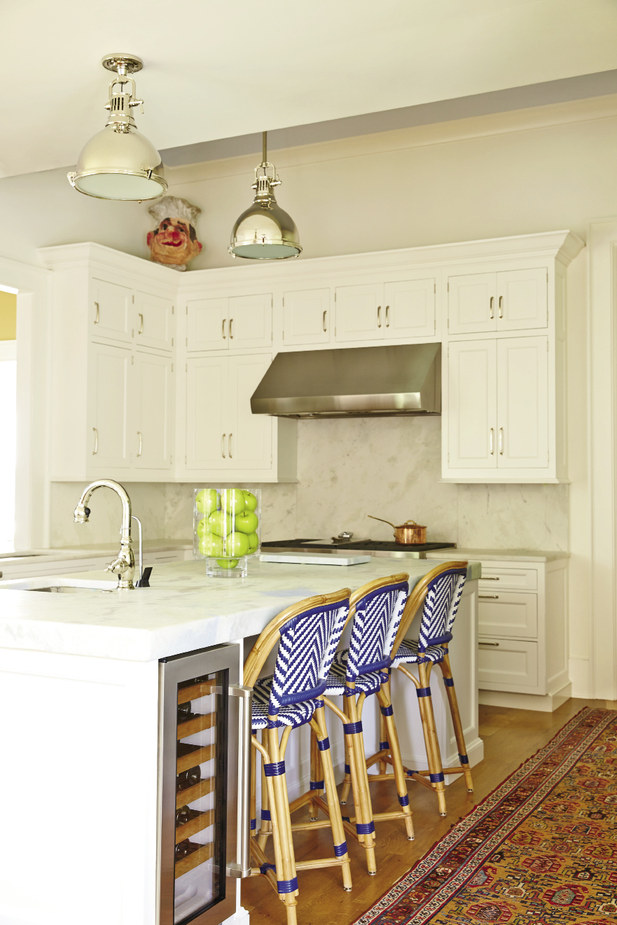 Custom Wood-Mode cabinets offer streamlined storage in the classic white-on-white kitchen, as well as in the adjacent casual family living space.