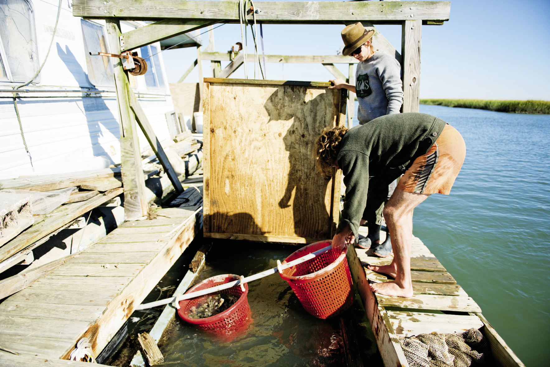 Caleb and Catherine set baskets of freshly sculpted Caper's Bay oyster singles into the water, where the bivalves will continue to grow and be purged of all grit and impurities.