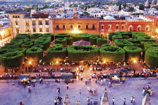 A view of the city's bustling central square, El Jardín, at dusk