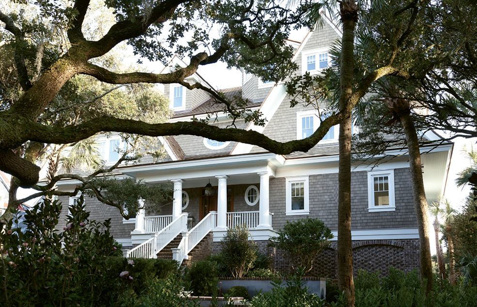 The front entrance to the shingle-style abode is shaded by old-growth oaks.