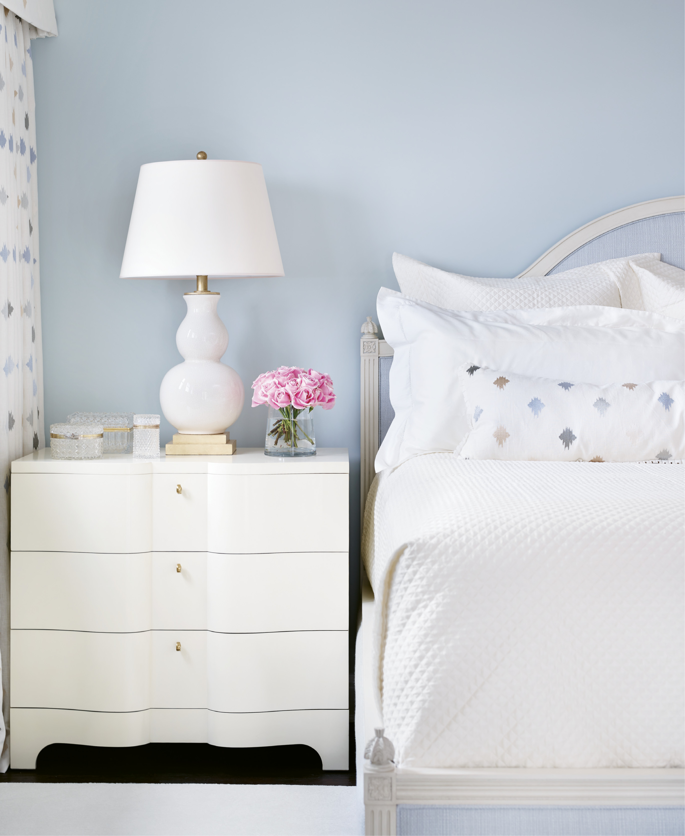 Another guest room offers a soothing blue palette echoed in the upholstered headboard.