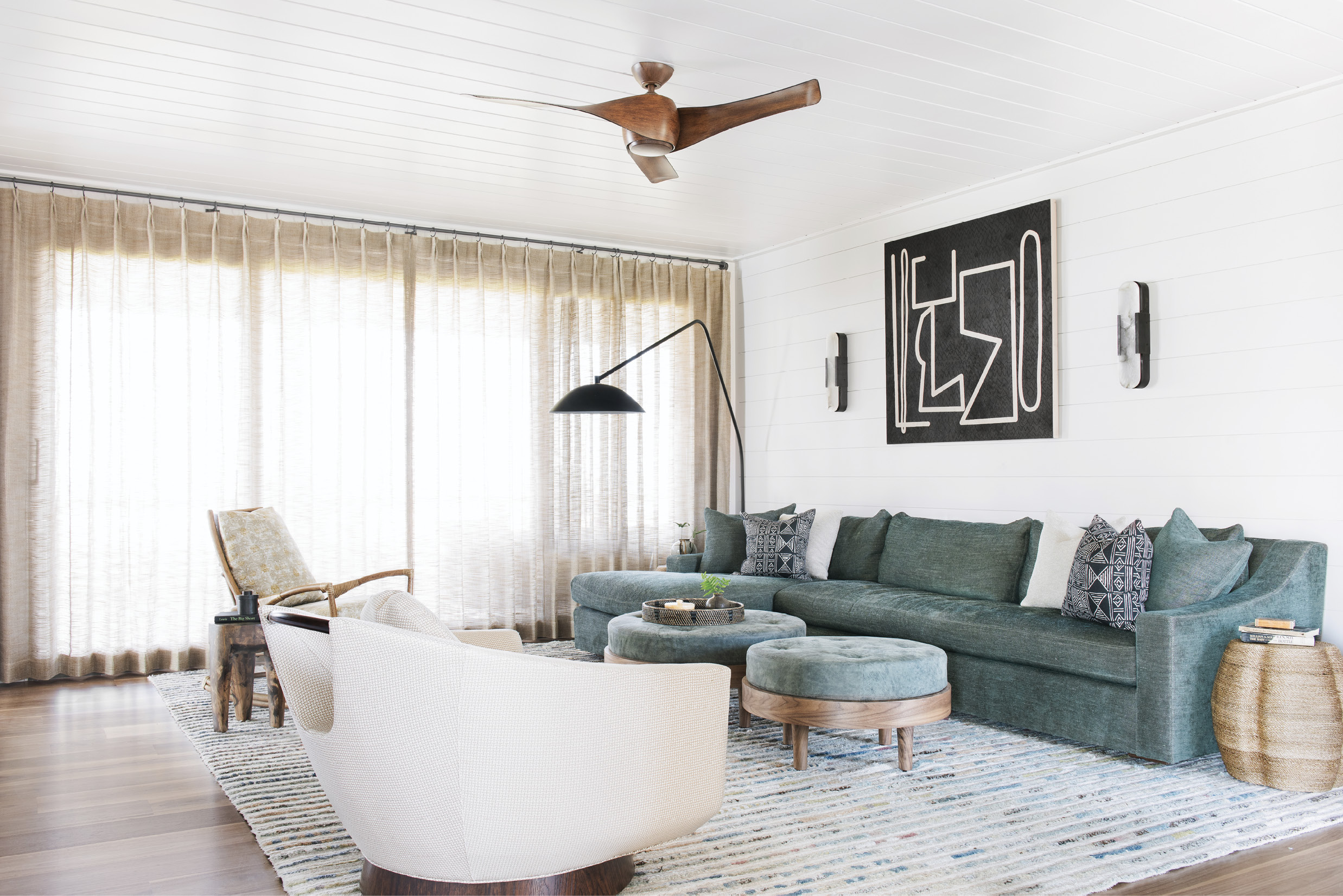 Cool Comfort: In the first-floor family room, an Amadi Carpets rug ties together an eclectic collection of furniture dominated by a Verellen sectional with matching ottomans. Kelly Wearstler for Visual Comfort sconces frame a black-and-white geometric painting by Brian Coleman from The George Gallery.