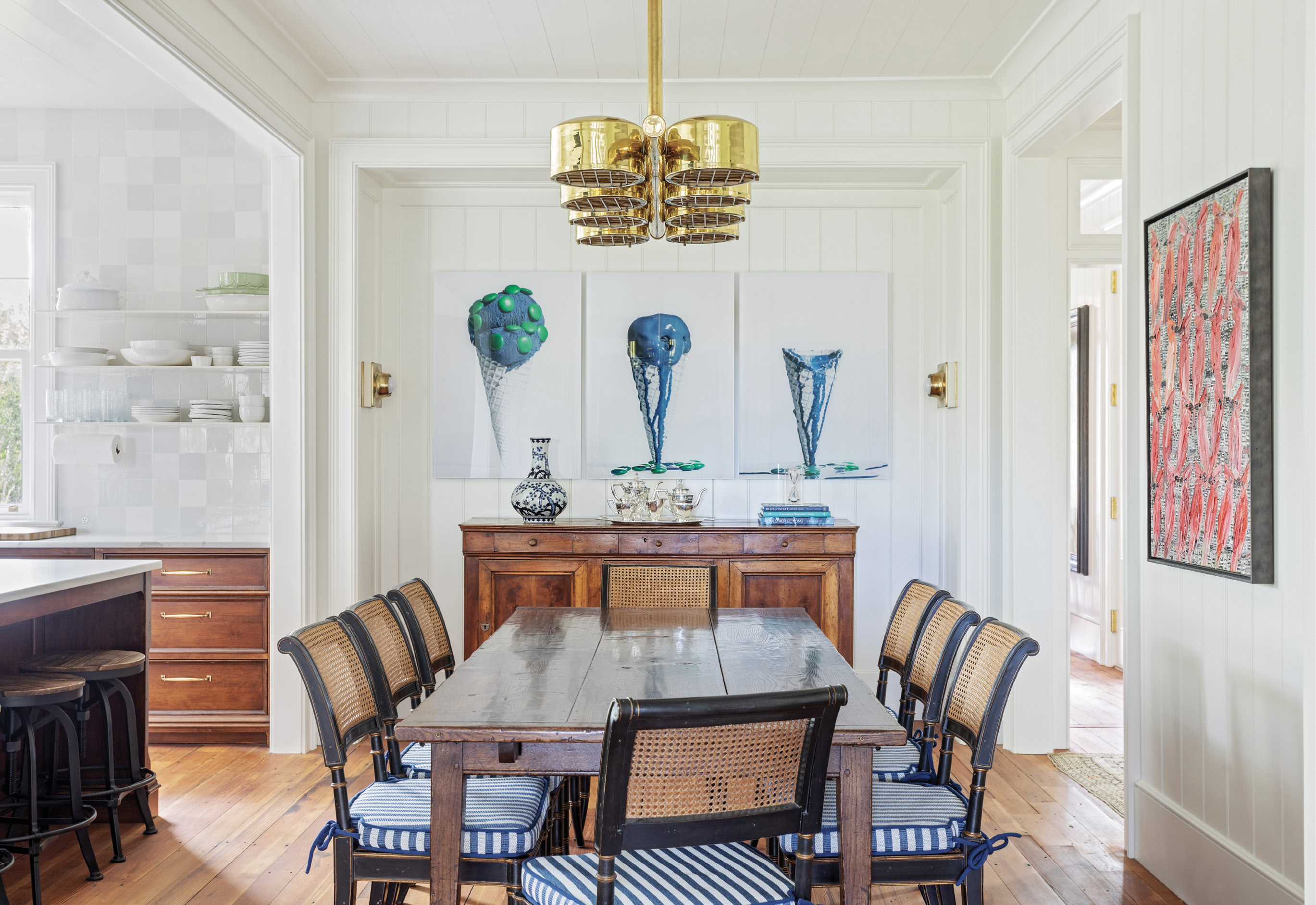 Thanks to the wife's expert eye and quick fingers on 1stDibs.com, a treasure trove of vintage and antique light fixtures complements the interiors. In the dining room, both the nautically inspired chandelier and brass wall sconces were sourced from the site, the latter to illuminate the melting ice cream triptych, Picture Global Warming, by Swedish photographer Clara Hallencreutz.