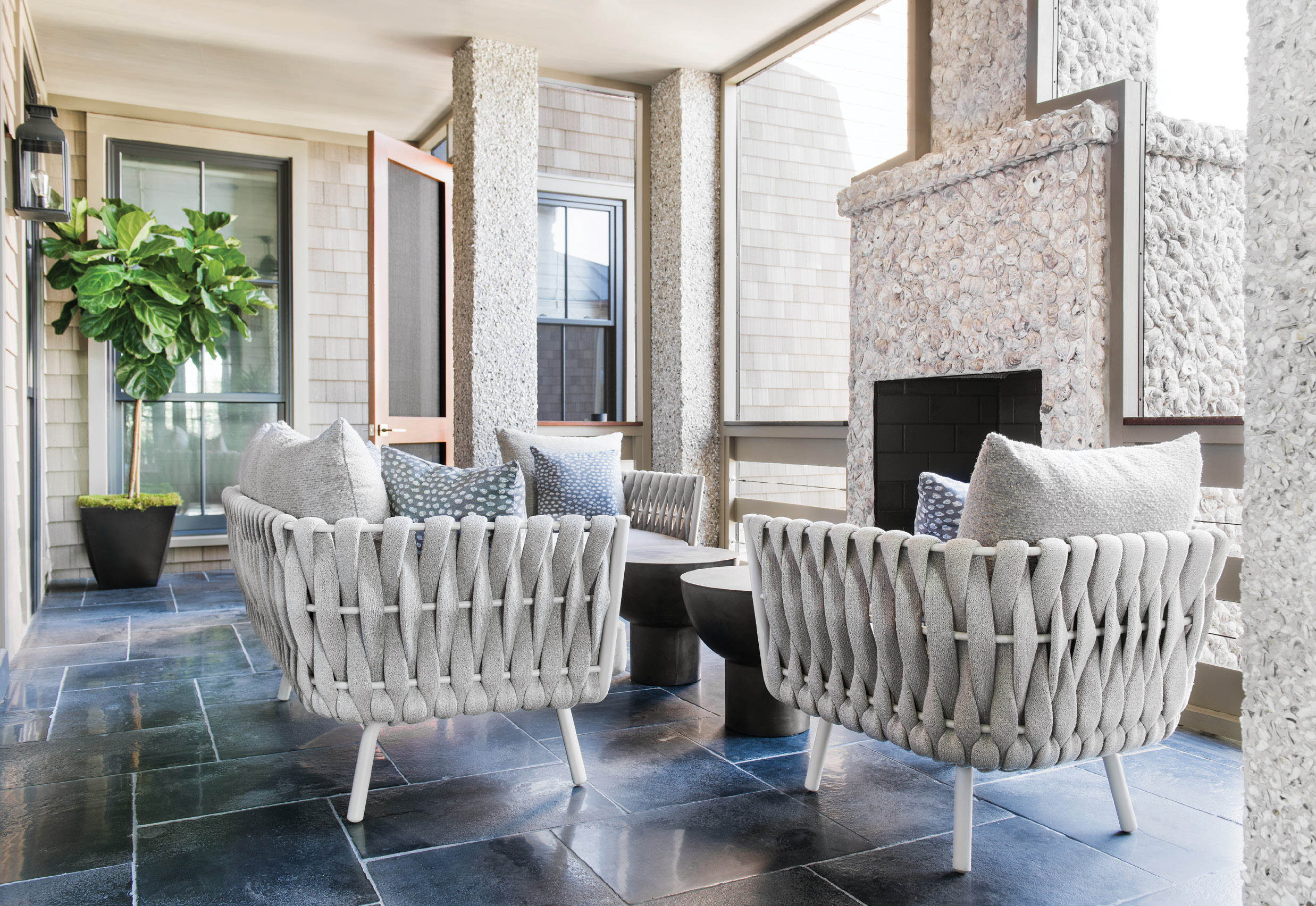 Shell Game: Stainless steel, textile-wrapped lounge chairs and a sofa from JANUS et Cie complement the simple yet dramatic second-floor porch, with its hand-thrown, oyster-shell fireplace and limestone flooring.