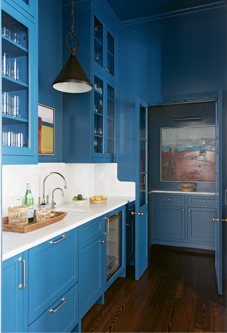 """BRIGHT SPOT: Cabinets lacquered in Benjamin Moore """"Blue Danube"""" pull the eye through the neutral kitchen into this daring butler's pantry. Two Sandy Ostrau works from Meyer Vogl Gallery add to the dramatic, contemporary feel."""
