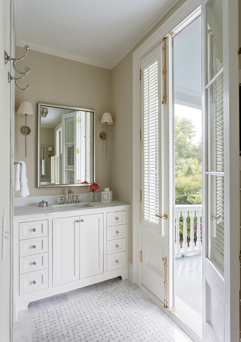 """SOAK IN THE VIEW: The downsized master bathroom prioritized access to the piazza over soaking space (there's no tub), keeping clean lines along with classic marble touches thanks to """"Melissa Wall"""" sconces by Urban Electric and a Calacatta basketweave tile floor."""