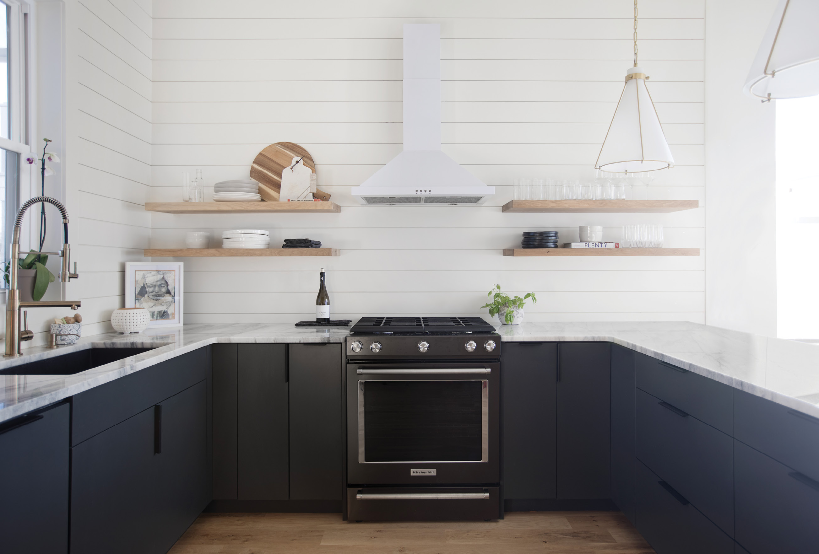 "LINEAR THINKING: Open shelving and shiplap walls create an inviting kitchen space that flows seamlessly from the adjoining dining area, replete with green velvet chairs by Moes (""They're so easy to clean!"" says Vickers). She chose shiplap as it's less expensive than a tile backsplash and helped with the continuity of the space."