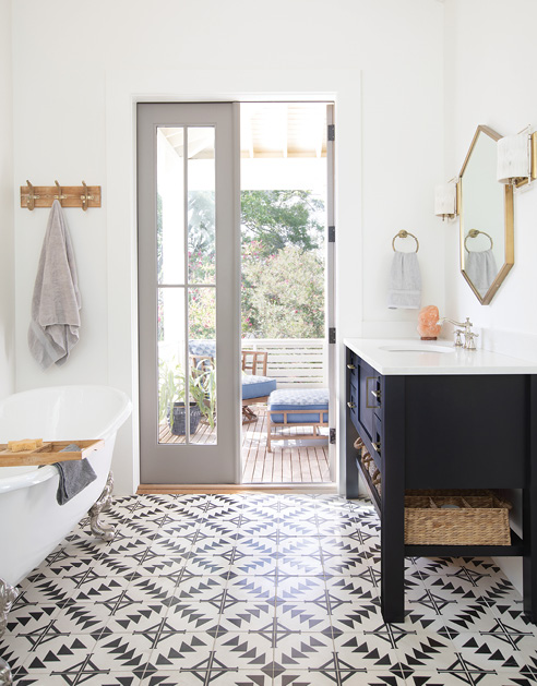 """The adjoining bath features the same tile as the kitchen backsplash, custom vanities by cabinetmaker David Beason, a clawfoot tub from Moluf's, and two """"Drake"""" hemp-wrapped brass wall sconces from Ro Sham Beaux. Both rooms open to a private porch outfitted with cushioned teak chaise lounges and chairs from Tommy Bahama."""