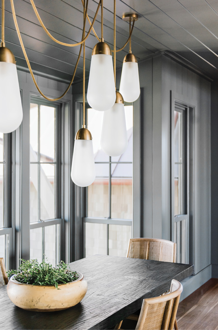 The dramatically painted dining room with a porcelain and brass chandelier by Apparatus
