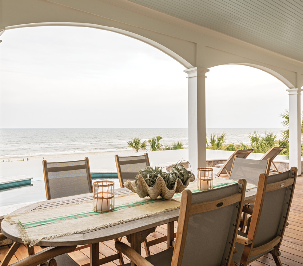 The porch dressed in chaise lounges and a dining set from Teak and Table, provides a shady spot where all generations of their extended families mingle—from the couple's young nieces to their parents.