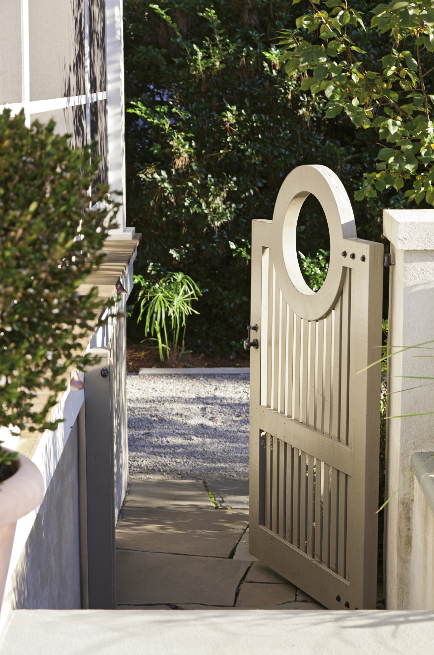 """The back gate leads into a verdant haven in the Old Village, where a subtly dramatic garden awaits, including rows of undulating boxwoods and """"hardy gardenia"""" azaleas."""