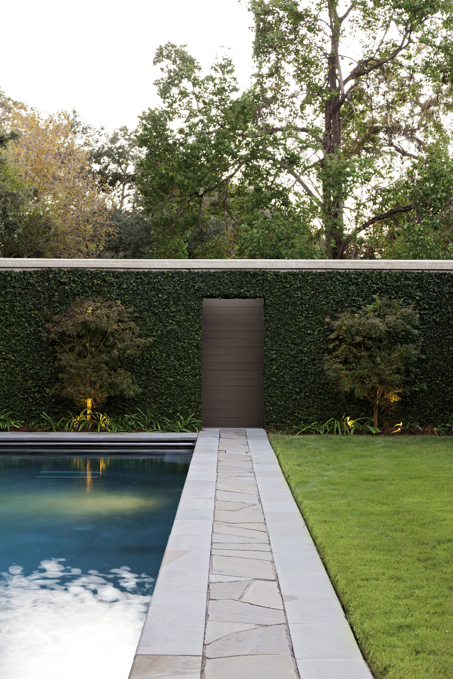 Green-leaf Japanese maples flank a door on the back garden wall, while a metal alligator adds a touch of poolside humor.