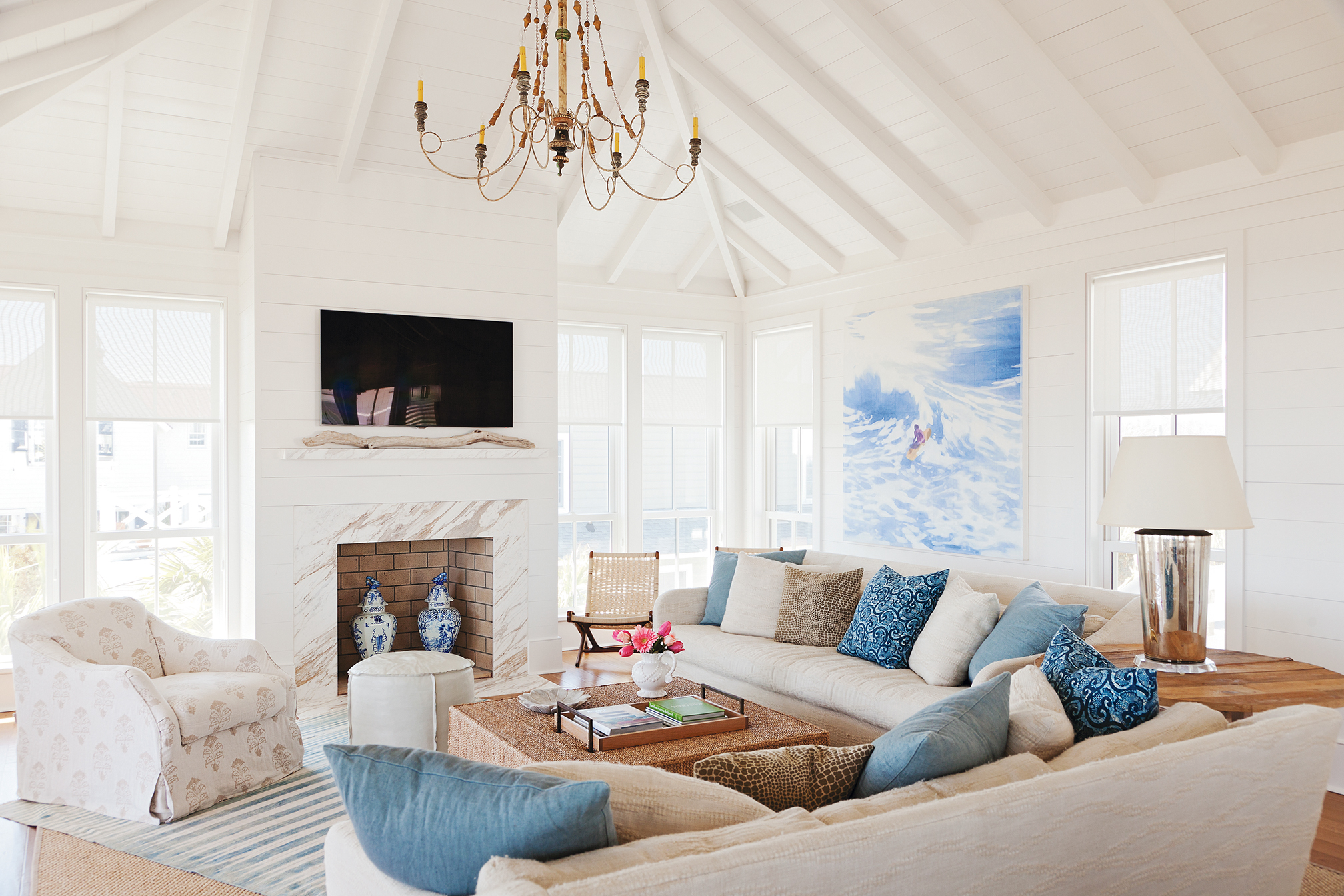 Old-School Charm: White shiplap walls throughout lend a classic beach-house feel while showcasing contemporary art, such as this surfer painting by Isca Greenfield Sanders in the living room.