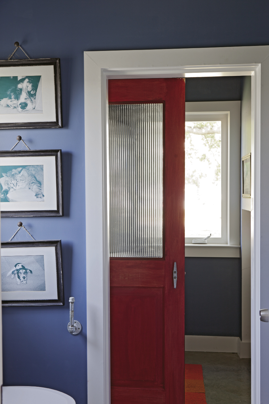 Mathis installed a door found at The Sustainable Warehouse in the first-floor bath, where it keeps the laundry room out of view.