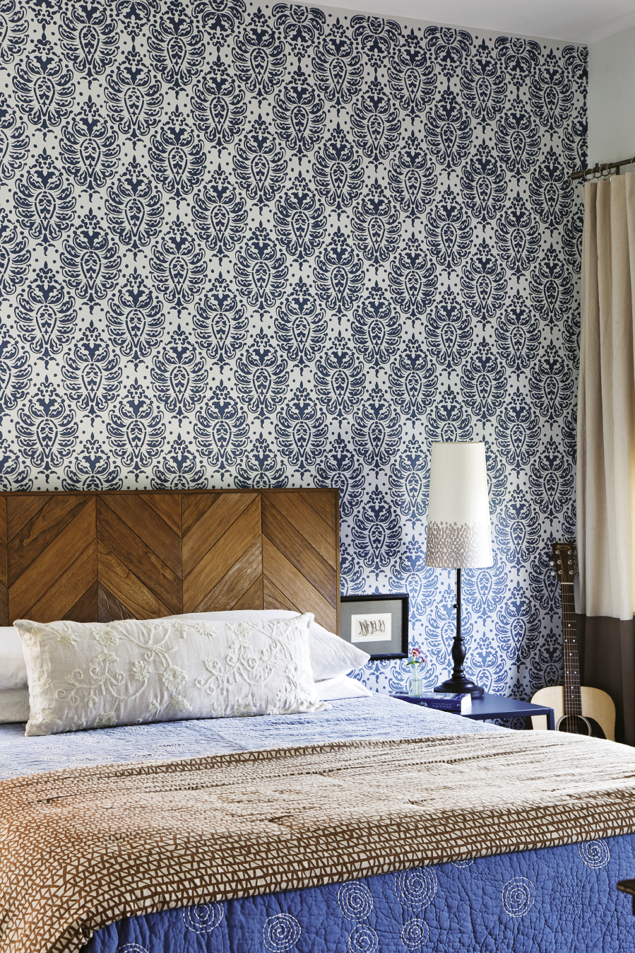 A repeating stencil pattern livens up the master bedroom; the penguin etching next to the bed was a gift from Mathis' sister.