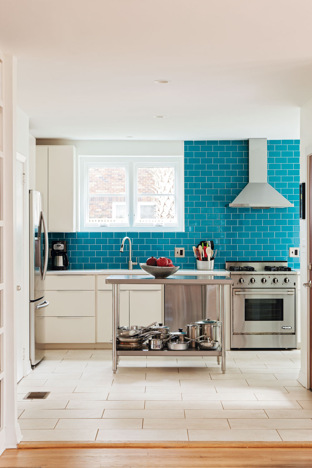 """COAT"" d'AZUR: A wall of bright blue subway tile delivers a splash of color to the modernized kitchen, with new stainless steel appliances, custom cabinets, and Daltile countertops."