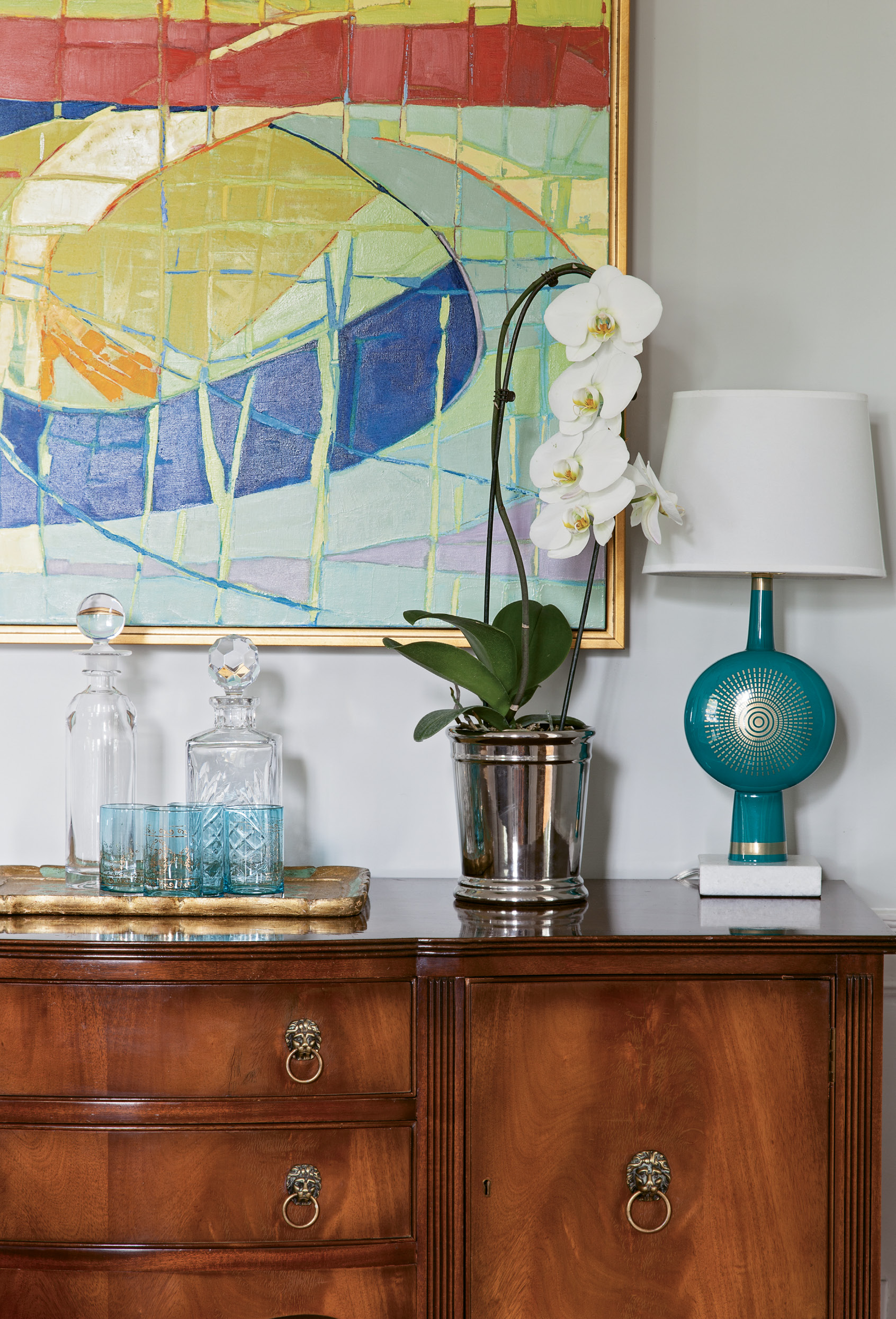 Shannon fell for this antique sideboard because its lion-head pulls mimicked the figurehead that has been mounted above the home's entryway since she was a child living next door. The painting is by fellow Charleston Artist Collective member Ann Keane.