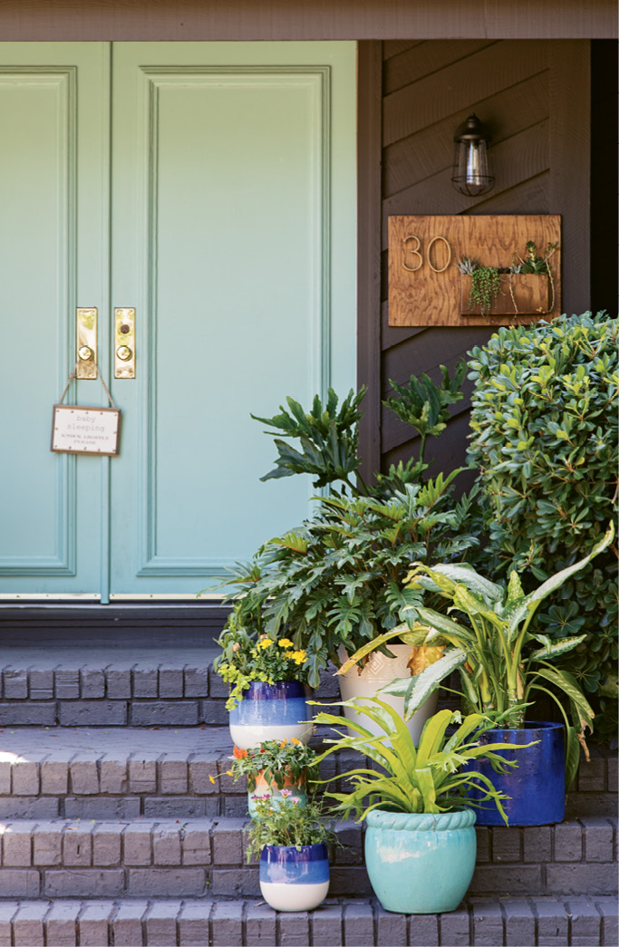 "The brick exterior was transformed with a charcoal shade called ""Ebony Fields;"" and the front door was given new life with a few coats of ""Tropical Bay,"" a statement-making turquoise."