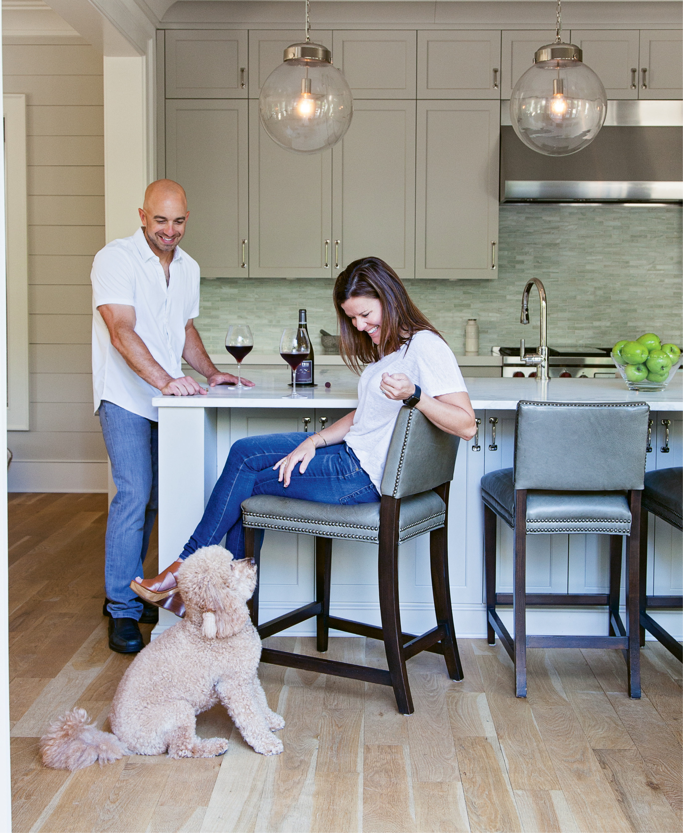 "His passion for all things food and wine were the driving force behind the kitchen design, including his insistence on an ""island that's almost too big,"" he says. Rusty, their mini Goldendoodle, blends in (adorably) with the unfinished white oak floors."