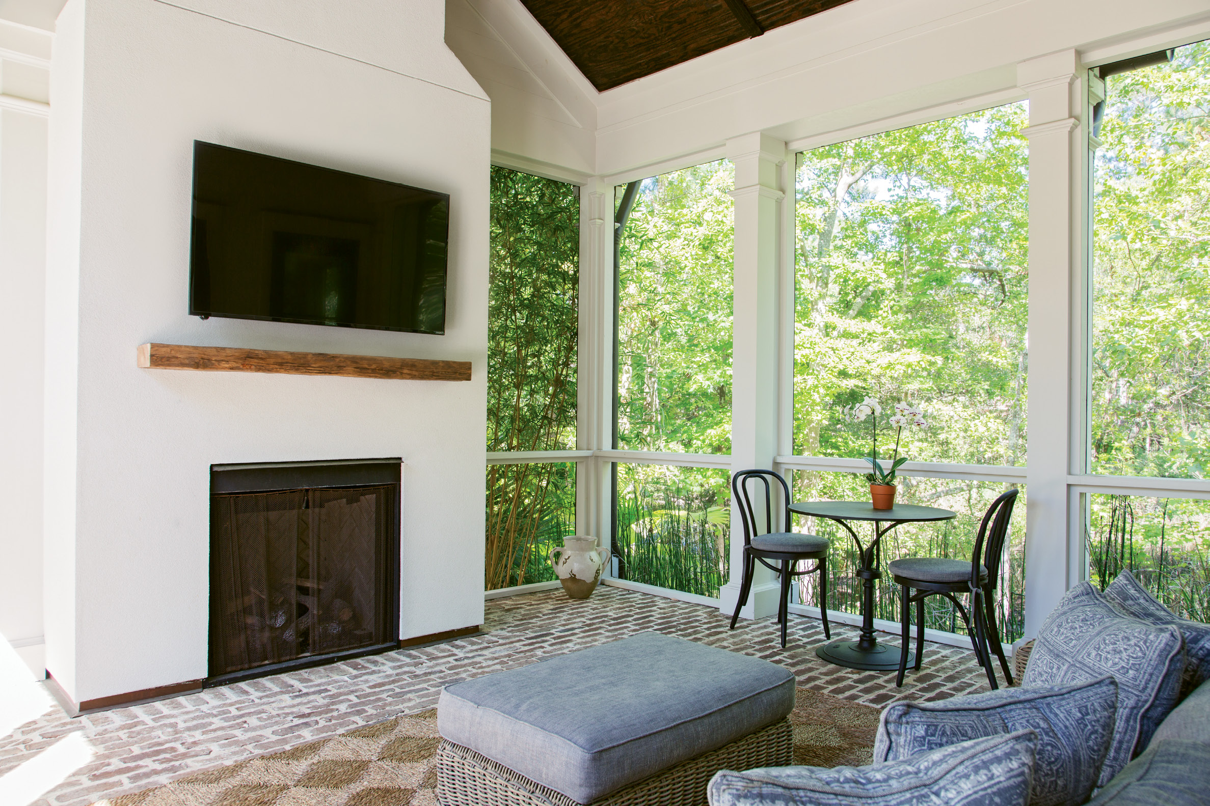 "Porch Peace: A screened back porch off the main living room opens both to the house and the courtyard, extending the sense of ""outdoor living,"" says Lenox. Old Savannah brick flooring adds earthy texture, and bamboo planted outdoors creates a natural screen. ""It's like you're encapsulated in the Lowcountry,"" Lenox adds."