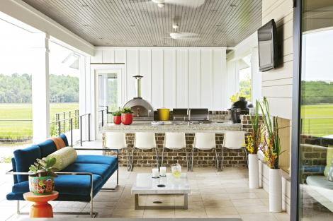 Seat Yourself: Ikea chairs line the bar in the outdoor kitchen. The marble coffee table and low-slung sofa were custom-designed by Deidre; the upholstery is a sturdy SilverState outdoor velvet.