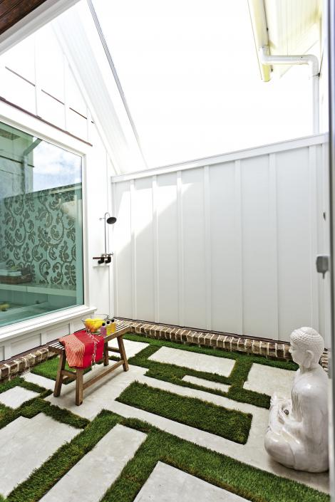 Concrete pavers are set in a geometric pattern in the outdoor shower adjacent to the master bath. The Buddha statue is by Cyan Design.