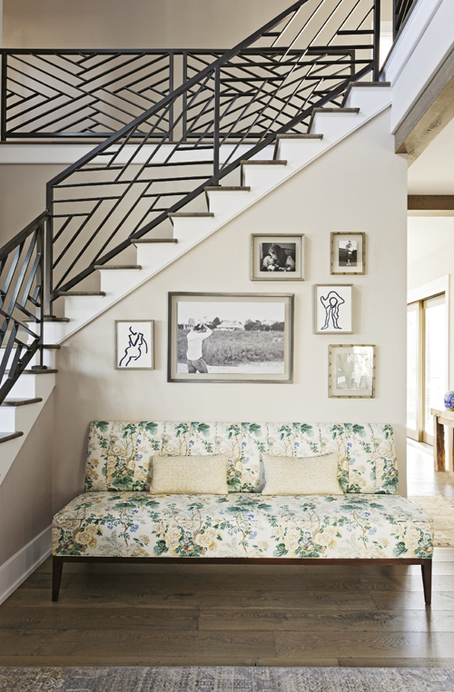 Modern Romance: The homeowners' clean-lined aesthetic, seen in the geometric patterns of the iron stair rails, is tempered by pieces that exude Old-World charm, like this floral chaise lounge.