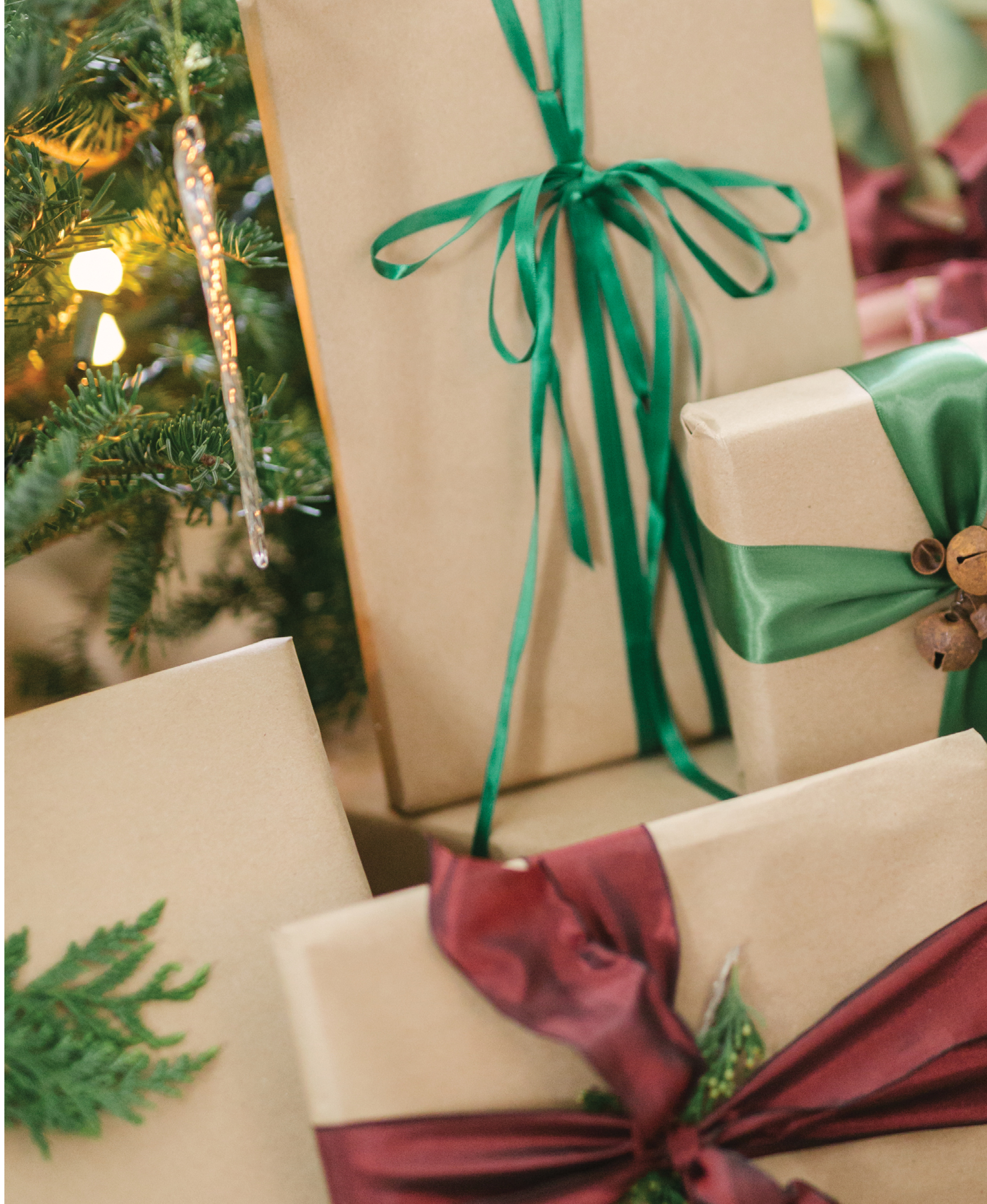 Color-coordinated gifts are wrapped in kraft paper and embellished with satin ribbon and an organic element, such as a snippet of fir, a cinnamon stick, acorns, or berries.