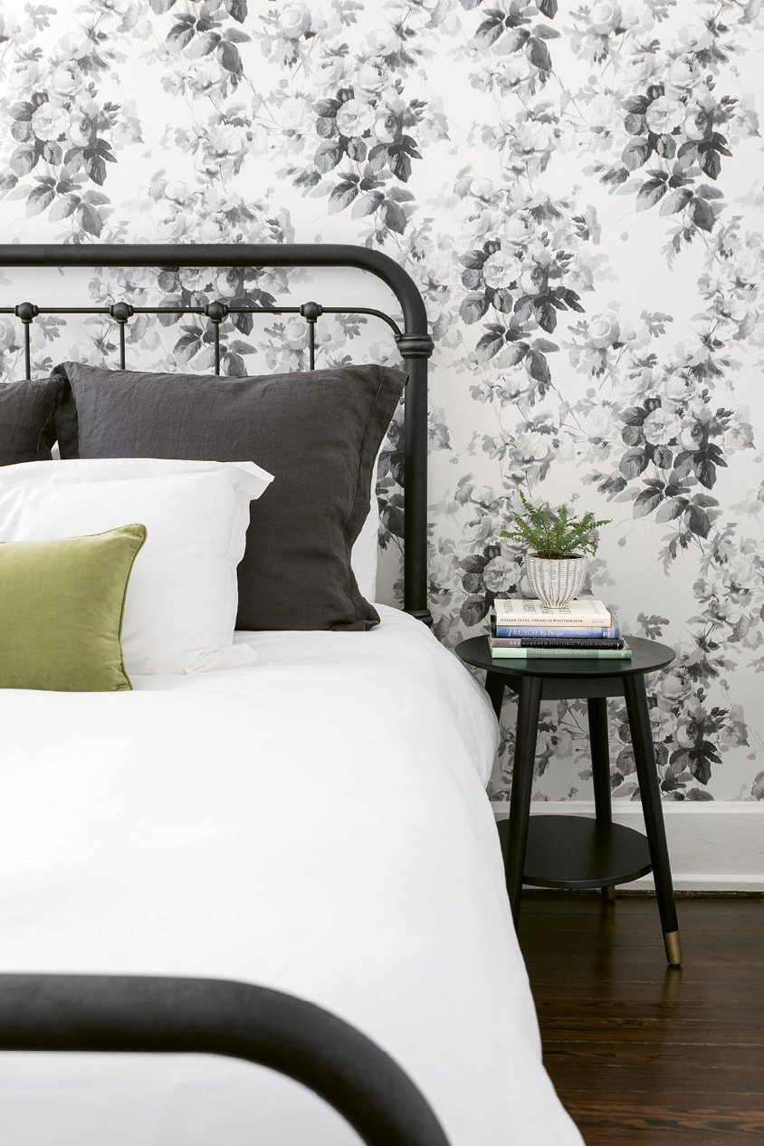 """SWEET DREAMS - Alison's mom visits often from Oklahoma, so a restful guest room was on the couple's wish list. A metal spindle bed from Celadon, crisp white bed linens, and a vintage bedside table—all layered against House of Hackney's """"London Rose""""-papered walls—delivers with aplomb."""