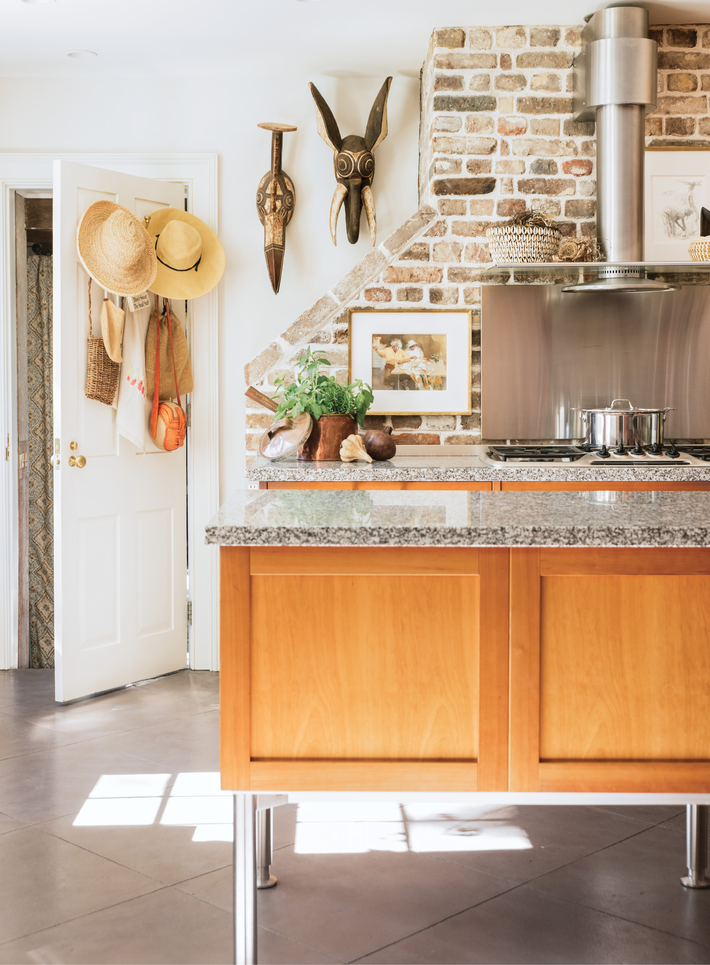 African masks and a watercolor painting by local artist Mary Whyte add warmth and personal meaning to the utilitarian, Bauhaus-style kitchen.
