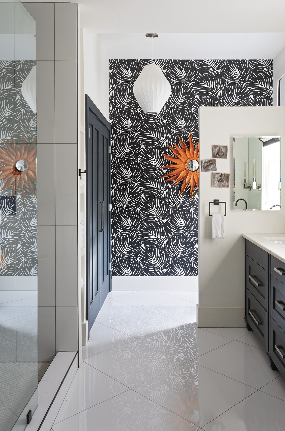 Space Saver: The master bath required significant reconfiguring—gone are the bathtub, window, and door to the piazza—to accommodate a closet, laundry room, and walk-in shower. An orange mirror provides a pop of color on the graphic palm frond wallpaper from Serena & Lily.