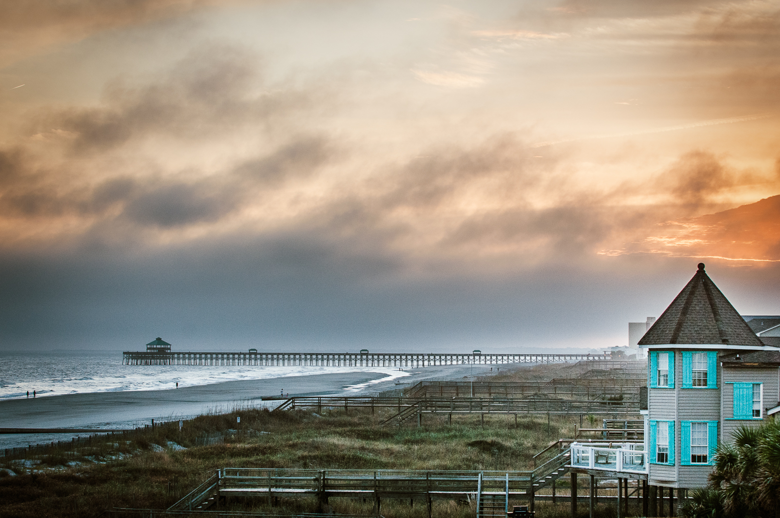 """HONORABLE MENTION Professional category: Folly Fog by Pamela Oliveras """"I drove down to Folly in January to capture the sunset and right as I got there a fog started rolling in. But it made the shot for me with the bit of the sunset orange pushing through and the blue of the beach house—gorgeous!"""""""