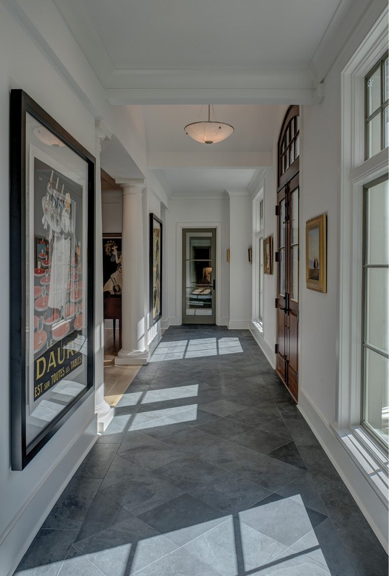 WELL FRAMED: Parallel linear foyers with floating walls to accommodate large paintings, bookend the main living area. Underscoring the home's symmetry, they provide excellent gallery space, this one showcasing vintage French Art Deco posters of Lotti, Cappiello, and Falcucci.