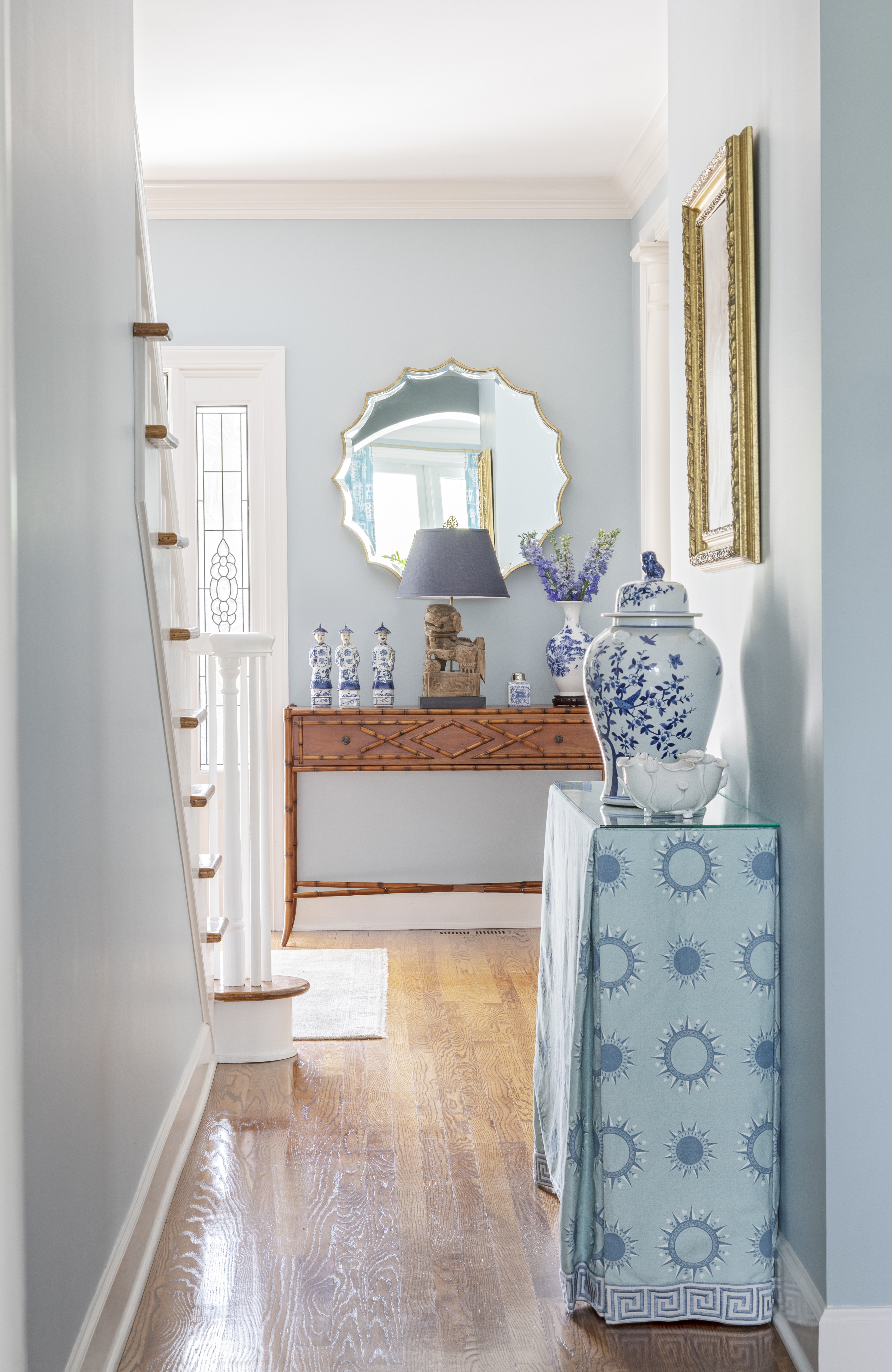 MIRROR MIRROR: A pair of matching console tables, skirted in fabric designed by Horton, display antique ginger jars from Well Furnished in the entry hall, where an aged brass mirror from Ballard Designs reflects the light from the marsh front windows to brighten the otherwise dark space.