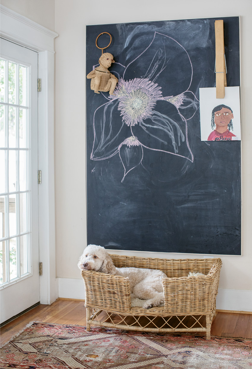 Doodle Approved: The wicker bed belonging to Ruby the Labradoodle sits beneath a chalkboard for family messages and artwork, such as 12-year-old Lily's self-portrait.