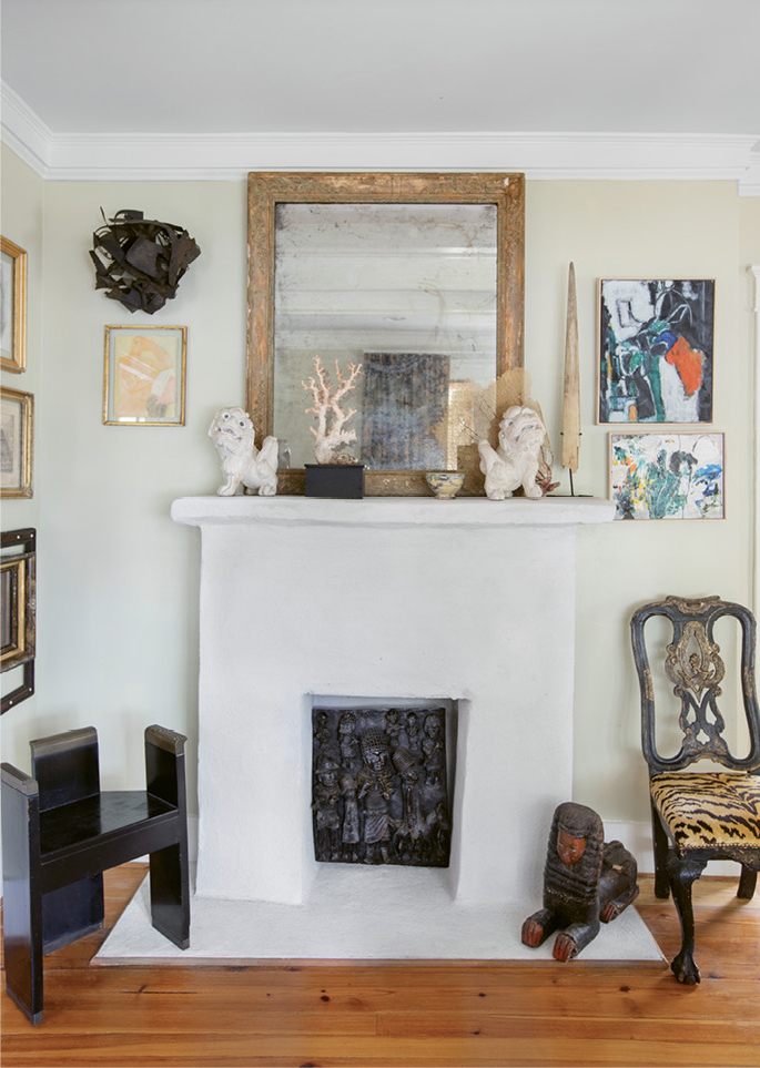 "in the mix: In the parlor, Debbie had the fireplace surround stuccoed and painted white for a clean, smooth effect that better showcases the melange of artwork and interesting objects she deems a ""necessary excess."""