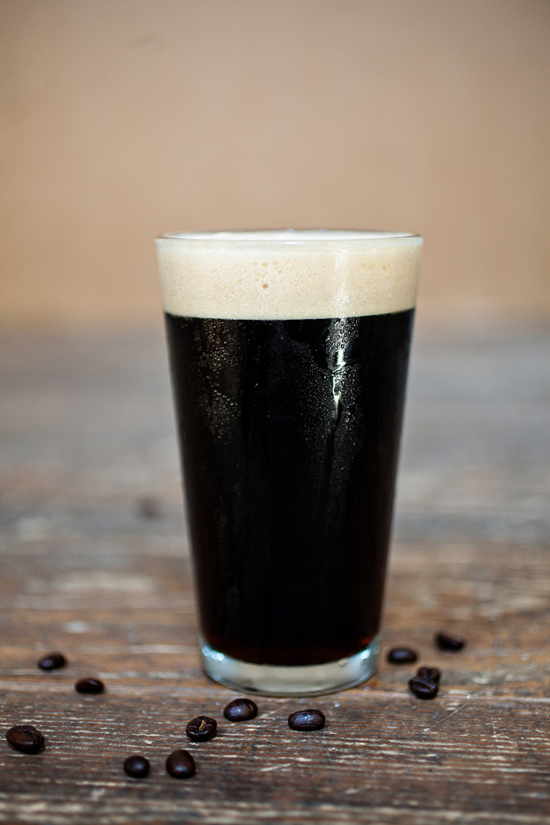 A Pint of Espresso Porter sits amongst coffee beans fromCharleston Coffee Roasters