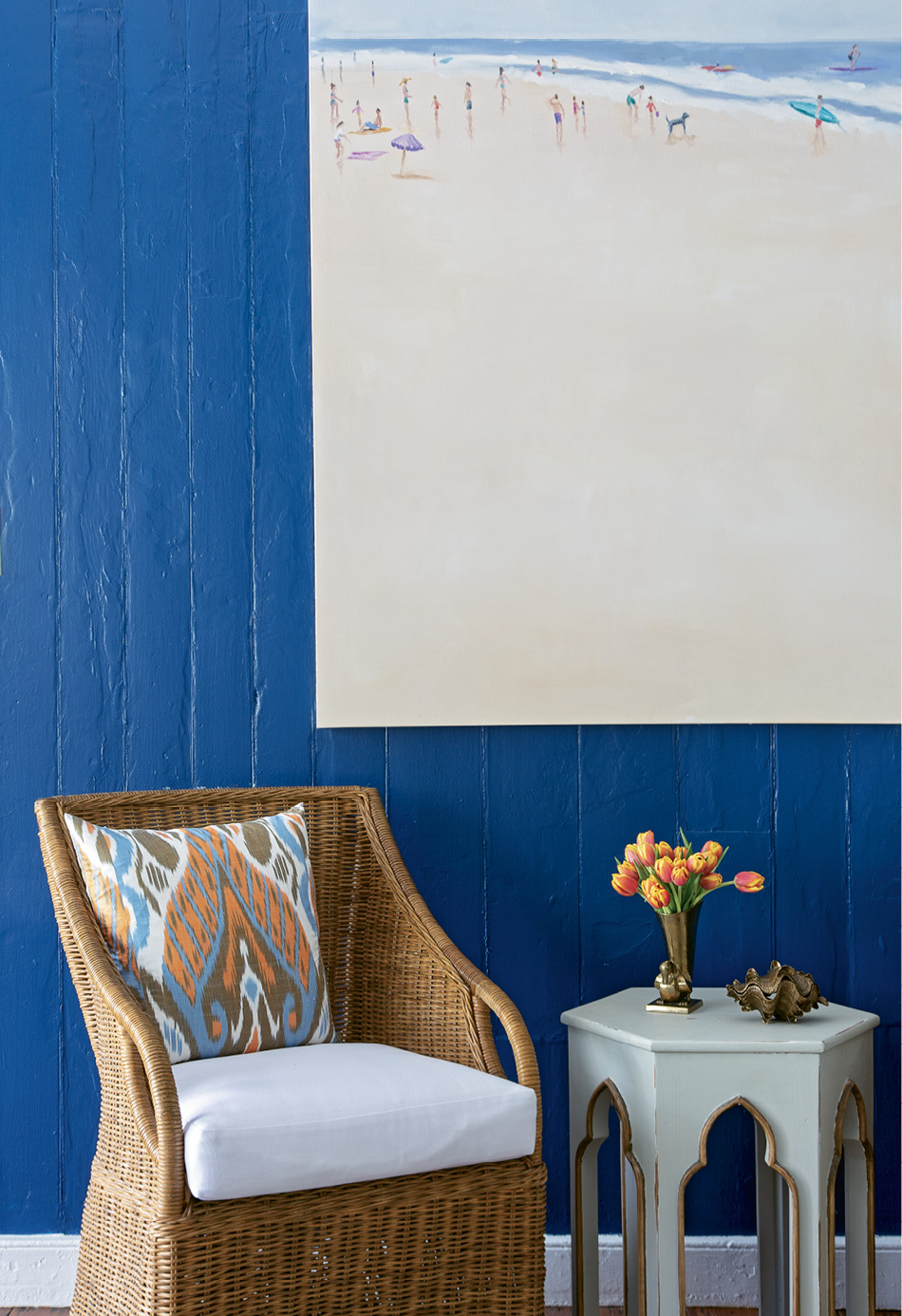 Serene Scene: Local artist Shannon Wood's expansive beach scene positively pops from the bold blue walls, a cheery welcome to the home. Beneath it, a Williams-Sonoma Home wicker chair invites visitors to sit and stay awhile.