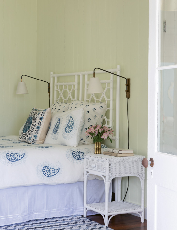 ...where a vintage white wicker headboard and table brighten the smaller space.