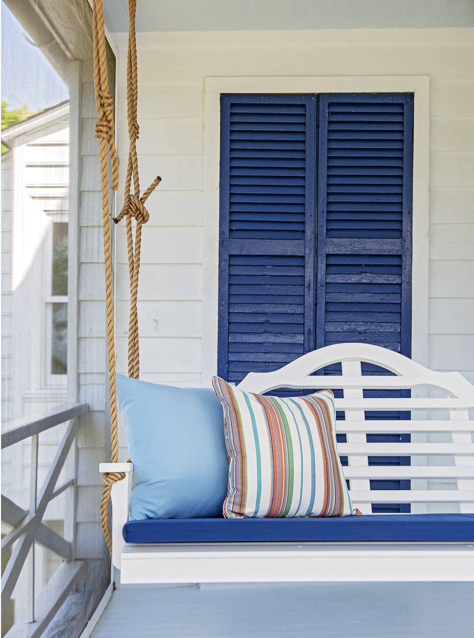 Sitting Pretty: No Southern porch is complete without a swing. A custom cushion matches the hue of the home's original shutters, which have kept this beachside abode safe from Mother Nature for more than a century