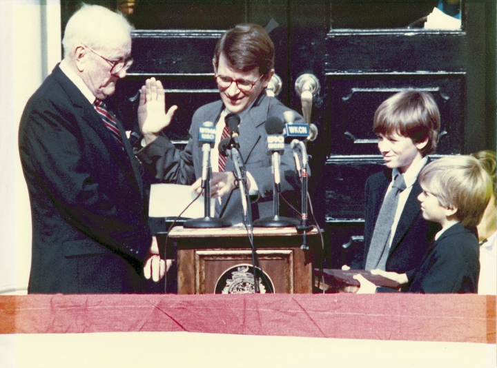 "Mayor Riley has taken the oath of office a record 10 times. He's pictured here in 1984 (his third term), with his father, Joseph P. Riley, Sr., administering the oath, and his sons, Joseph and Bratton (far right), by his side. When Joe III did the honors for his father in January 2012, he inserted some humor by beginning the oath with, ""So, for the last time…."""