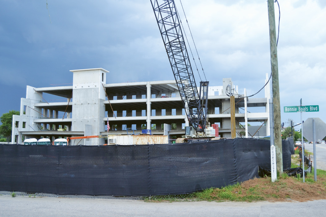 The controversial office building and parking garage being erected at Coleman Boulevard and Mill Street