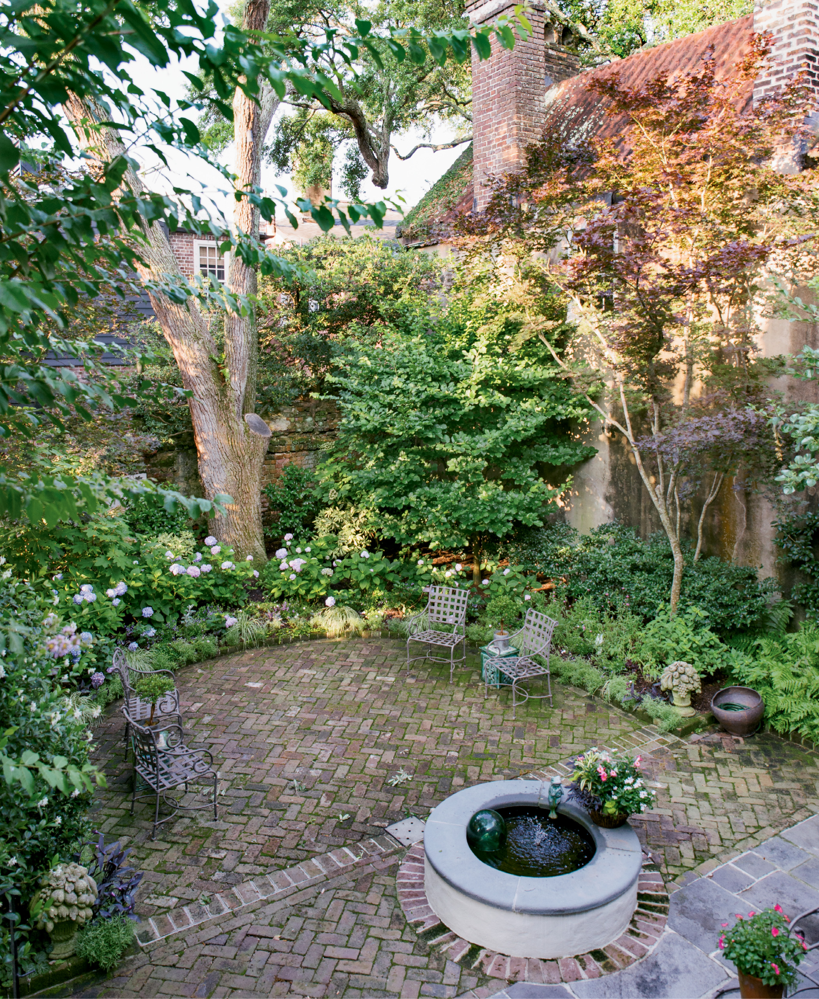 Mature oak, parrotia, Japanese maple, and fringe trees lend privacy and shade to the courtyard garden.