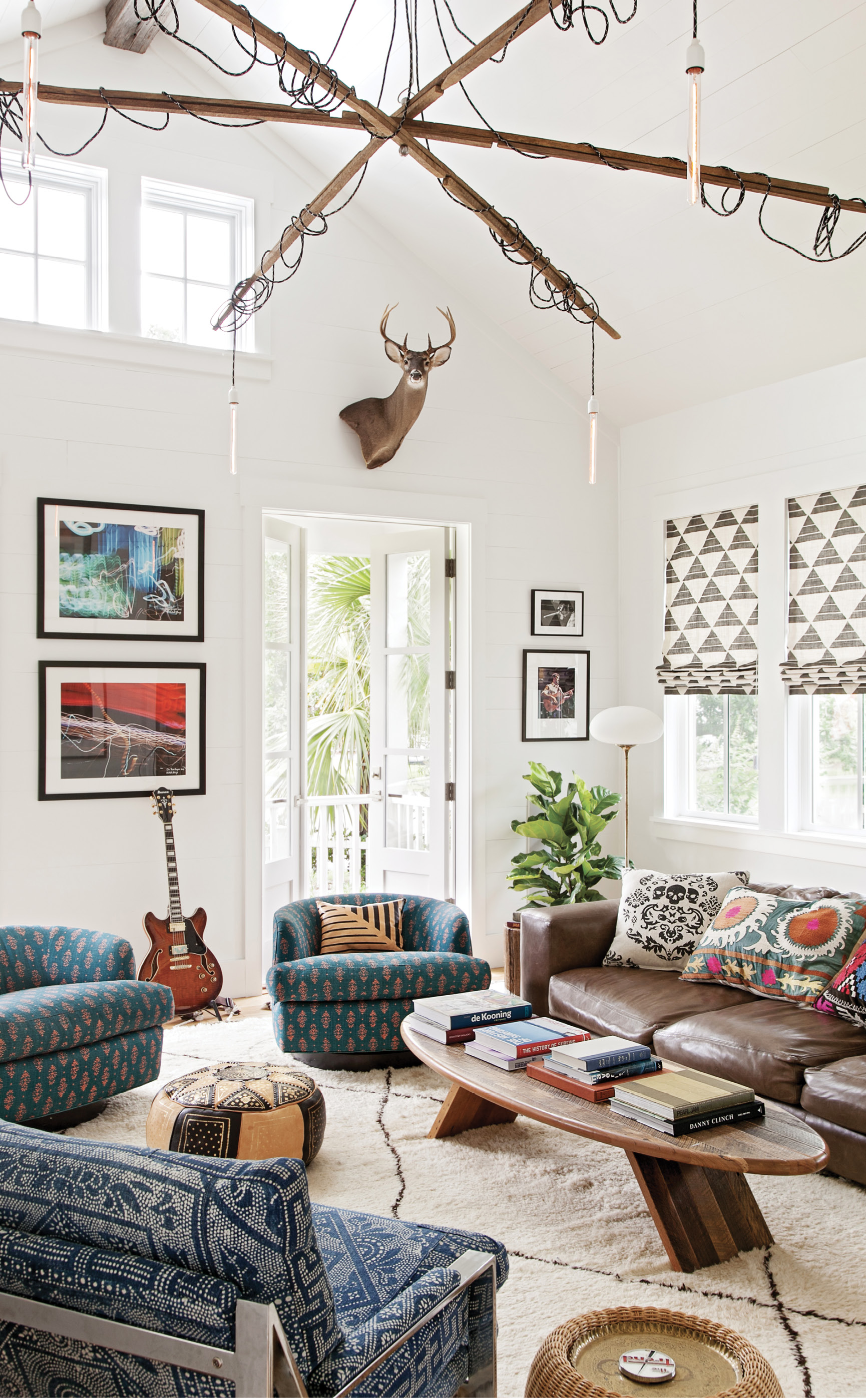 """HOME, SWEET HOME: The family room is the Keenans' haven. Modeled on the former sweet shop that occupied the lot, its tall walls and vaulted ceilings provide plenty of space to showcase the couple's photography collection and custom Jeff Jones tobacco stick chandelier (""""We literally built this room around that fixture,"""" says Keenan, only half-jokingly.)"""