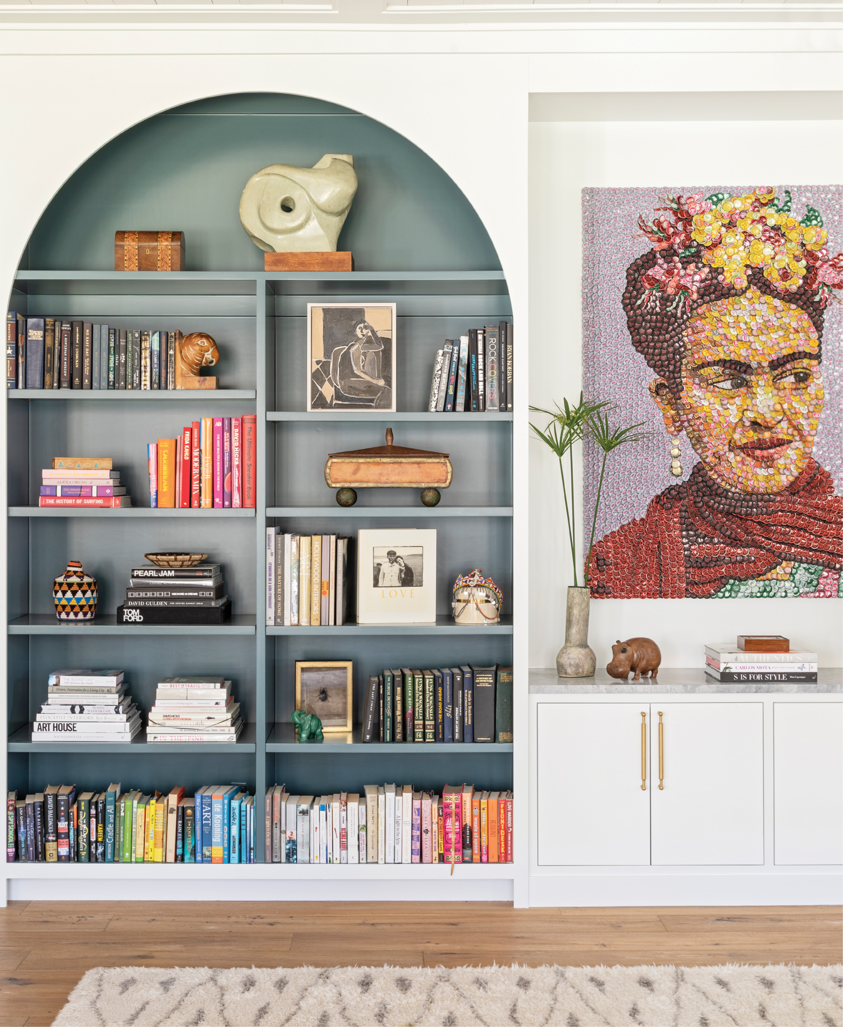 """Top Shelf: Adding built-in bookshelves to the living room brought order to the room while providing a pop of color courtesy of Farrow & Ball's """"Inchyra Blue."""" The custom design also beautifully showcases local artist Molly B. Right's bottle-cap homage to Frida Kahlo. A brass and wicker side table from Hollywood at Home and vintage shearling chair from 1stdibs add texture and dimension."""