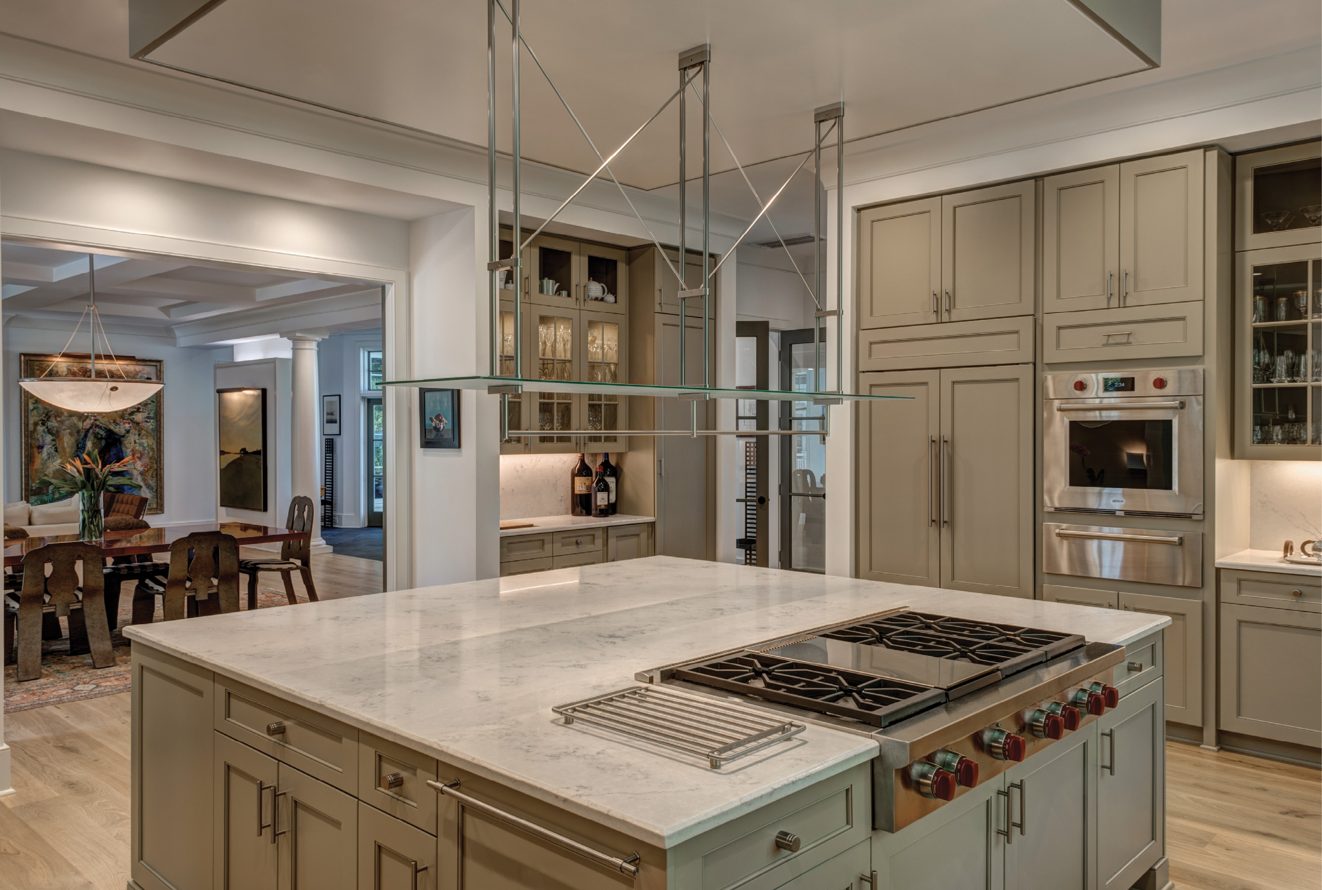 """COOKING LIGHT: Abundant natural light is the main ingredient in the spacious kitchen, where an oversized island with quartz countertops offers a central gathering space. """"We entertain a lot,"""" says the wife, who loves to cook but gives her husband props for """"approaching chef status"""" with his culinary expertise."""
