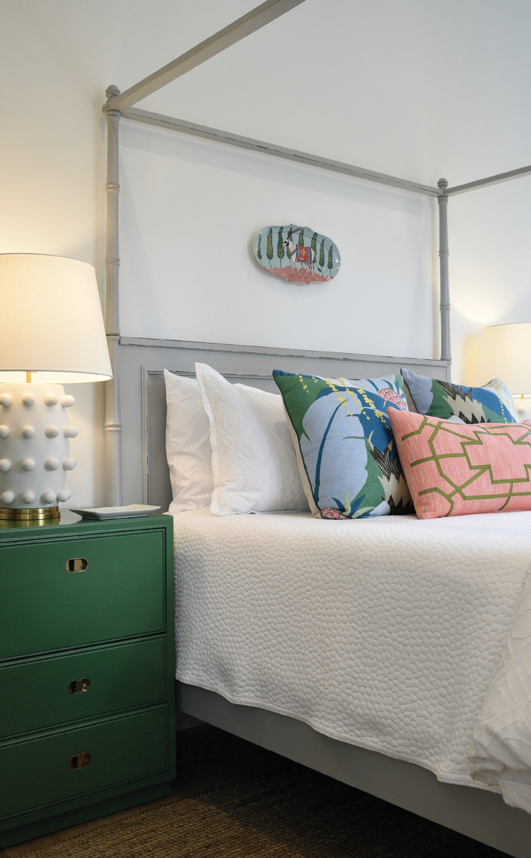 "PASTEL PERFECT: The Braggs's 15-year-old daughter, Ella, is ""very opinionated"" about her room, helping Alix design the space by combining the reproduction bamboo tester bed with the pillows in Schumacher's Ananas print, both from Acquisitions Interiors, and her mom's vintage side tables. The doors of the green-lacquered beauties fold down to provide the perfect spot for charging her phone and squirreling away clutter."