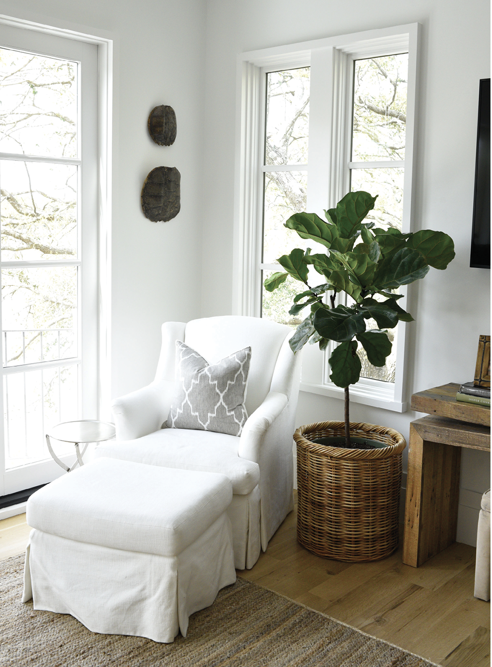 The white chair and ottoman from Acquisitions Interiors makes for a cozy reading nook in the bedroom.