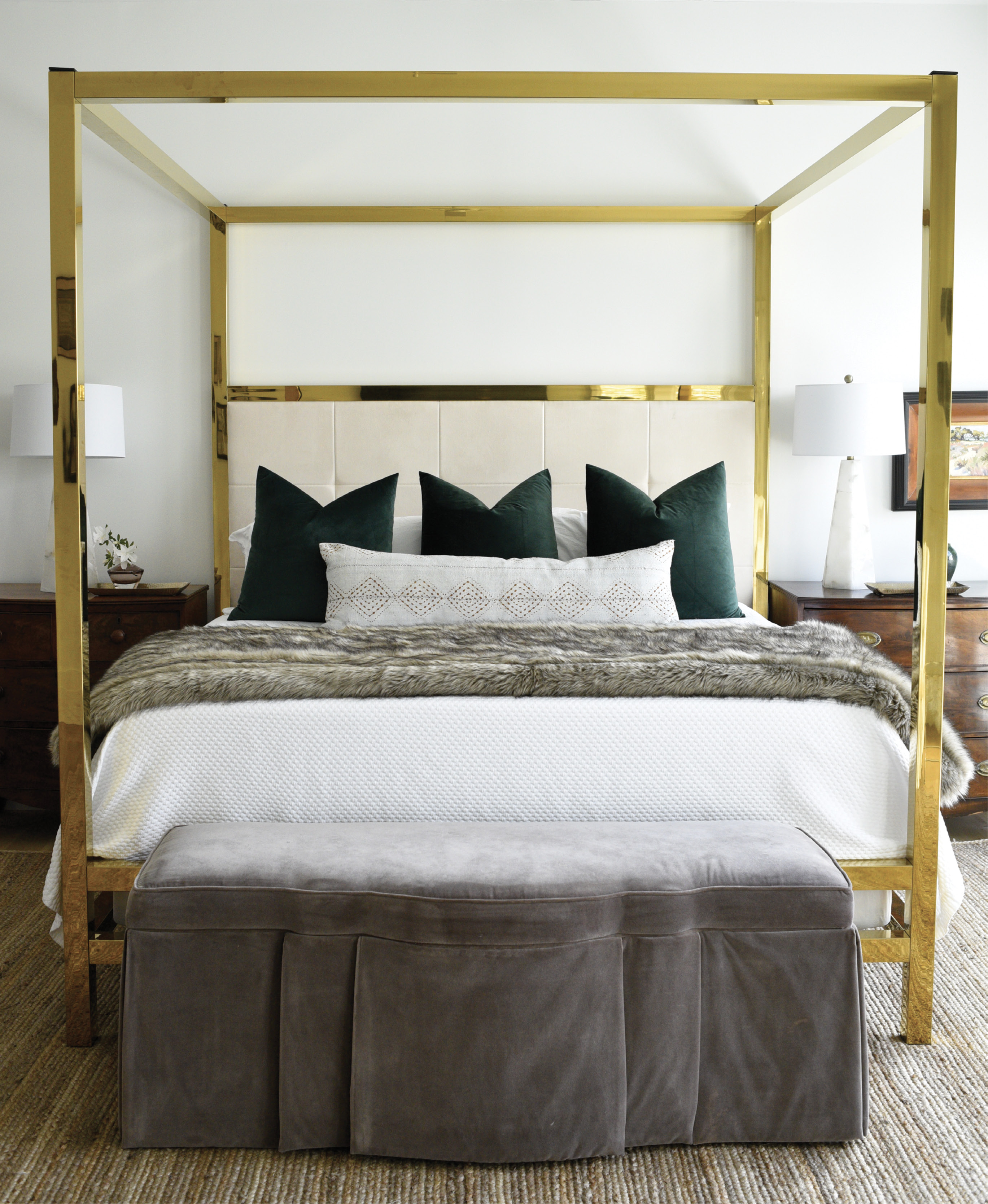 Alix's love of brass extends to the master bedroom where this vintage four-poster bed makes a big statement. Dramatic green velvet pillows stand out against the custom sueded headboard as well as Matouk bed linens from GDC Home—all capped off by a velvet footstool from Acquisitions Interiors.